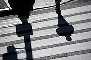 shadows of person waiting to cross the road