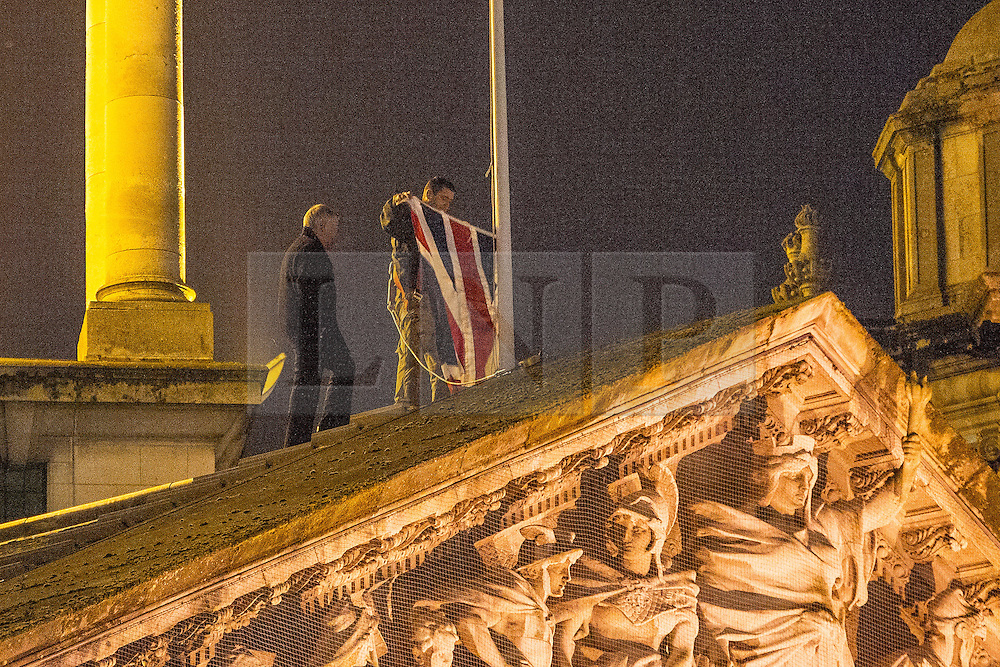 © Licensed to London News Pictures . 09/01/2013 . Belfast , UK . The Union Jack flag is lowered at Belfast City Hall this evening (9th January 2013) . It had been raised to mark the Duchess of Cambridge's 31st birthday . On 3rd December , councillors voted to limit the number of days the flag would be flown , sparking weeks of violence . Photo credit : Joel Goodman/LNP.
