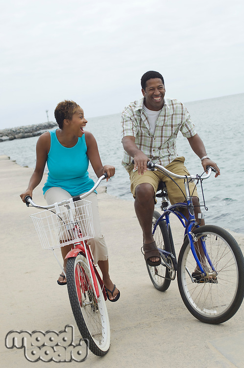 Middle-aged couple cycling at promenade