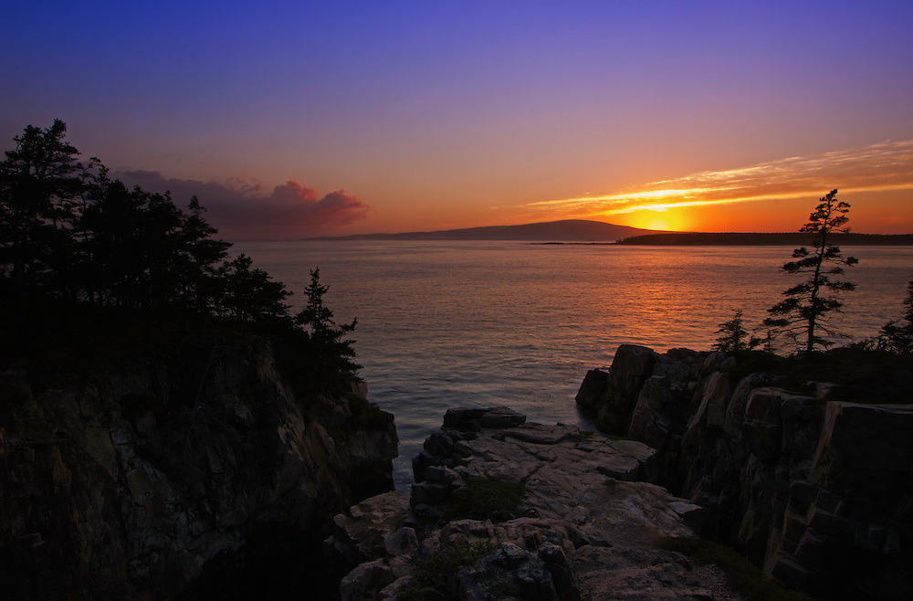 Coastal Maine seascape photography at sunset featuring a spectacular view across the beautiful cliffs at Schoodic Peninsula towards Cadillac Mountain in Maine Acadia National Park. This coastal spot is secretly tucked away in the much less crowded portion of the national park. The area is dramatic and unmarked and unpromoted by the national park for its steep and dangerous cliffs. I finally made a return journey to the only area of the national park that is located on main land. With tripod and camera positioned at the edge of the steep cliff in front of me I captured Cadillac Mountain Sunset.<br />