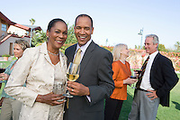 Couple holding drinks at outdoor party, portrait