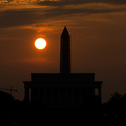 The sun rises over silhouettes of the Lincoln Memorial and the Washington Monument on Washington DC's National Mall.