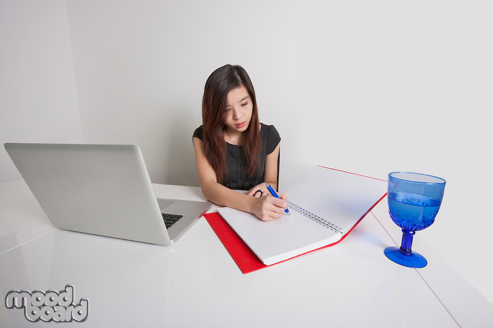 Young businesswoman writing on diary at office desk