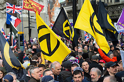 © Licensed to London News Pictures. 09/12/2018. London, UK. Demonstrators hold yellow and black American US far right Identitarian movement flags at a pro-Brexit march, organised by UKIP. The march took place three days before parliament's crucial vote on Theresa May's deal. Photo credit: Ray Tang/LNP