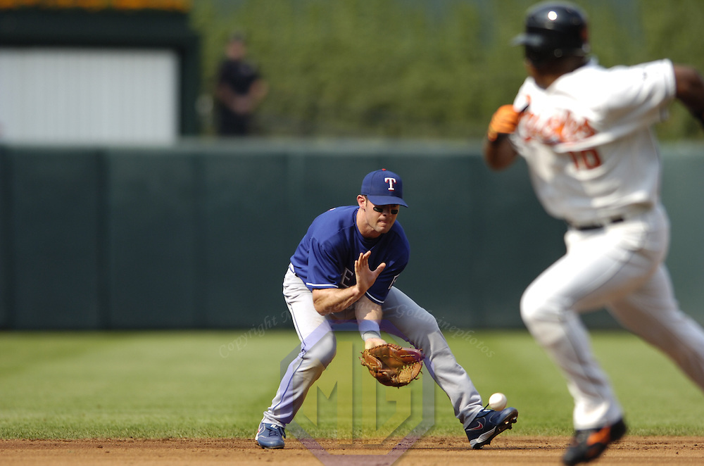 15 July 2006:  The Texas Rangers' Michael Young (10) fields a ground ball in the 1st inning hit by the Baltimore Orioles Jeff Conine as Miguel Tejada (10) moves to third base.  The Orioles defeated the Rangers 8-1 at Orioles Park at Camden Yards in Baltimore, MD.