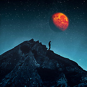 Surreaö nightscape witk a man in front of a rock and an orange moon/planet in the sky