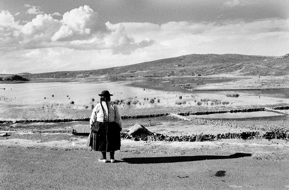 198 / Eine Frau und ein Schatten am Titicaca See in Peru: SUEDAMERIKA, PER, PERU, CUZCO, 01.09.2000:Eine Frau und ein Schatten am Titicaca See in Peru. - Marco del Pra / imagetrust - Stichworte: Anden, Cuzco, Frau, Landschaft, Model Release:No, PER, PERU, Property Release:No, QUETSCHUA, Schatten, schwarz, See, Stichwort, SUEDAMERIKA, Zoepfe, Zopf, weiss, Titicaca, Titikaka,