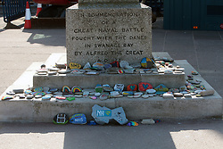 Covid-19 - Stones painted in support of the NHS, placed at the base of the King Alfred commemoration column in Swanage Bay Dorset. Coronavirus lockdown UK April 2020