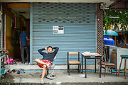 "12 DECEMBER 2012 - BANGKOK, THAILAND:  A demolition worker relaxes in front of the empty business he lives in while he works at ""Washington Square"" a notorious entertainment district off Sukhumvit Soi 22 in Bangkok. Demolition workers on many projects in Thailand live on their job site tearing down the building and recycling what can recycled as they do so until the site is no longer inhabitable. They sleep on the floors in the buildings or sometimes in tents, cooking on gas or charcoal stoves working from morning till dark. Sometimes families live and work together, other times just men. Washington Square was one of Bangkok's oldest red light districts. It was closed early 2012 and is being torn down to make way for redevelopment.    PHOTO BY JACK KURTZ"
