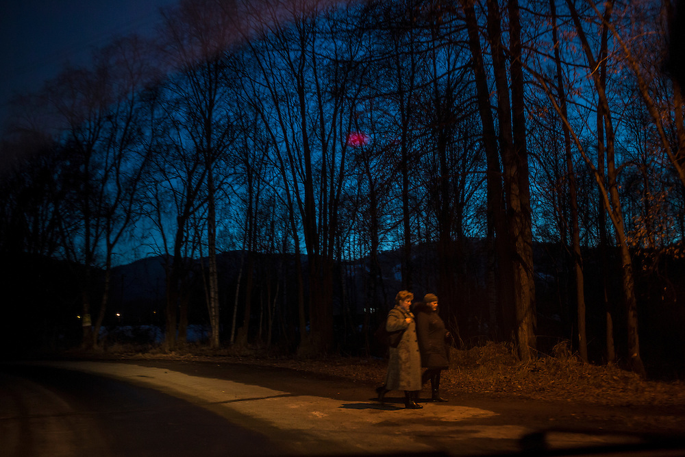 Two women cross the road on Saturday, October 19, 2013 in Baikalsk, Russia.