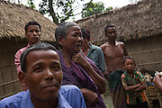 Dhonobala Rani, 70, gets emotional knowing that in a few months she will have to leave her son (front blue shirt) behind in Bangladesh when she takes Indian citizenship. <br /> <br /> Living in Ponchoki Bhajini village located inside the enclave of Dhoholakhagrabari her son Shankor Rani, 32, missed the Indian verification registration in 2011 who came to take details of everyone who lives in the enclaves in Bangladesh and those that want to leave. As a result his wife, child and himself cannot be included and is not allowed to move to India with the rest of his family.<br /> <br /> On July 31st 2015 the enclaves that formed one of the world's most complicated borders were officially absorbed in to the countries that surrounded them in a land-mark land swap between India and Bangladesh. The people that lived in them will finally receive citizenship.<br /> <br /> Enclaves are small pockets of sovereign land completely surrounded by another sovereign nation. Approximately 160 enclaves, known as chitmahals, exist on either side of the India-Bangladesh border. For 68 years the 50,000 plus inhabitants of these enclaves have lived a difficult existence, stranded from their home nation and ignored by the country that surrounds them. <br /> <br /> In theory even leaving their enclaves is illegally crossing an international border and for decades it has been very difficult for them to receive even the most basic of rights whether education or health. Even the police have no jurisdiction in the enclaves leaving them essentially lawless.