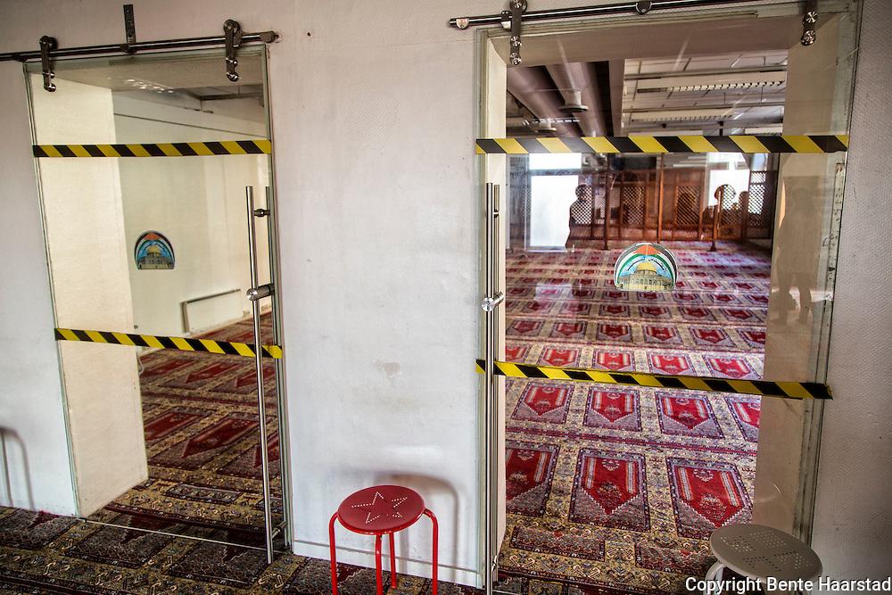 Kvinneavdelingen i Rabita-moskeen i Oslo, sett fra hovedavdelingen, dvs. mennenes område. Dørene inn til kvinnene er avsperret med sperrebånd. Kvinnene har egen inngang, og sitt eget areal, og de får ikke bevege seg foran tregitteret, bakerst i  det anviste arealet. Men de kan kanskje skimte imamen gjennom glassdørene i front.