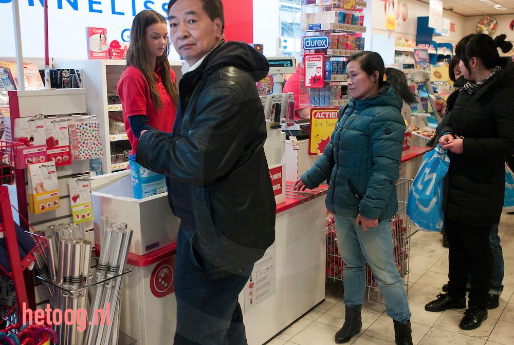 Netherlands, Nederland, Enschede 04mrt2015 Een grote groep Chinezen en/of mensen van Chinese afkomst tezamen met enkele nederlanders koopt melkpoeder in een filiaal van drogisterij Kruidvat in Enschede. Na afloop verlaat men met tassenvol Nutrilon van producent Nutricia  de vestiging. Bij ontdekking van de fotograaf wordt deze belemmerd in het maken van foto's en belt men terstond de politie.