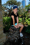 Child (10 years old) sitting on one of two bronze lions, known as Temple Dogs, in Royal Botanic Gardens. Sydney, Australia