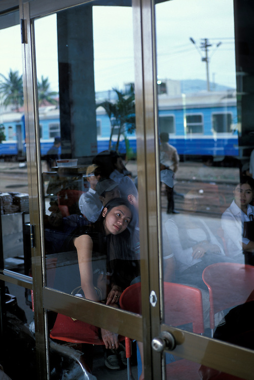 Asia, Vietnam, Hué, Woman sits in Central train station as Reunification Express train arrives