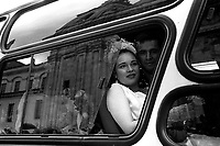 A newly married couple, who had a joint ceremony with over 100 other officers from the Colombian Police force, wait to be bused off for a joint wedding celebration in downtown Bogotá. (Photo/Scott Dalton)