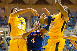 Jan 12, 2016; Morgantown, WV, USA; Kansas Jayhawks guard Devonte' Graham (4) West Virginia Mountaineers forward Esa Ahmad (23) and West Virginia Mountaineers forward Elijah Macon (45) all collide in the lane during the first half at the WVU Coliseum. Mandatory Credit: Ben Queen-USA TODAY Sports