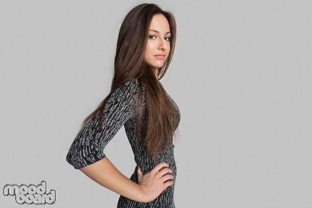Side view portrait of confident girl against gray background