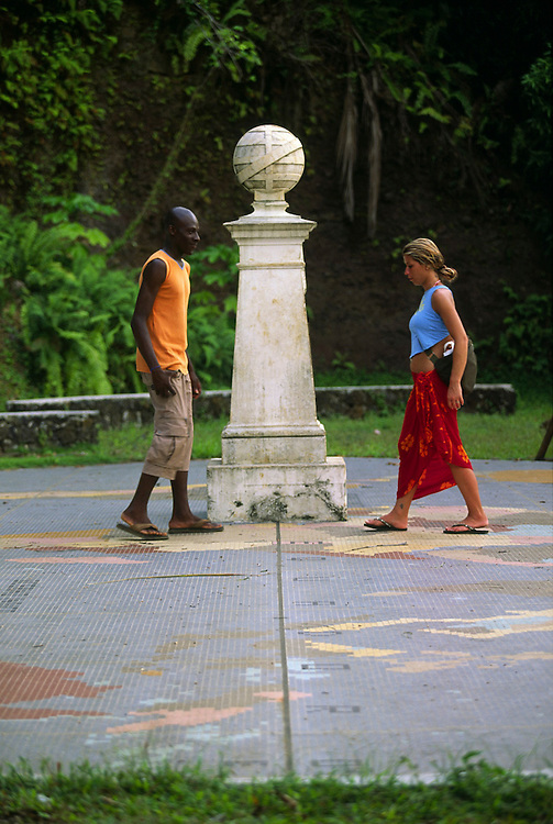 A young man and a young girl stand on each side of the equator line. He is on the southern hemisphere and she is on the northern hemisphere