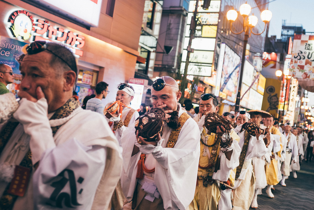 A street procession in the Dotonburi neighborhood of Osaka, Japan.