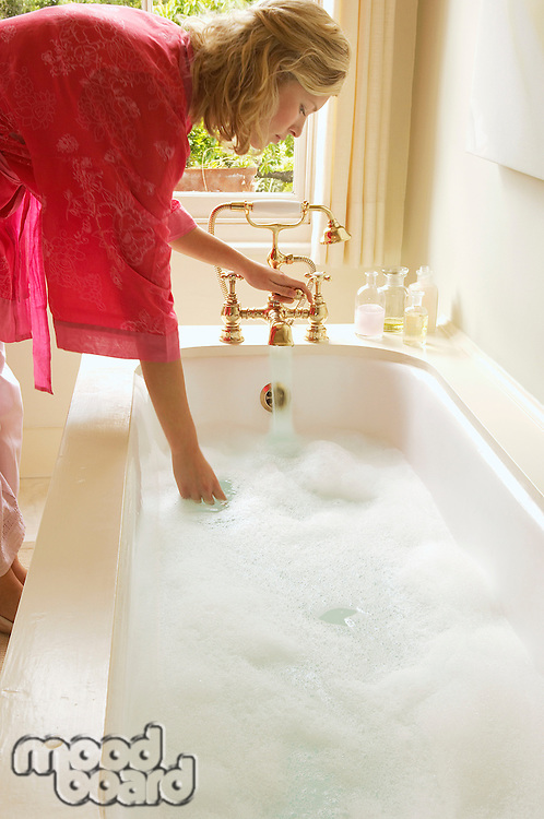 Woman in bathrobe bending down over bathtub filled with bubbles testing water side view