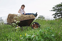 Girl (5-6) sitting on hay in wheelbarrow in field