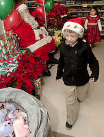 Seven year old Adam Watson heads to Santa's goodie bag after having a chat with the man himself describing the remote control spy camera he wants for Christmas at Heath's Supermarket in Center Harbor Friday evening.   (Karen Bobotas/for the Laconia Daily Sun)