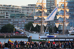 "© Licensed to London News Pictures. 06/09/2015.  The banks of the River Thames were packed with spectators to see the Colombian flagship ARC Gloria go through Tower Bridge to celebrate Colombia Day. The three masted sail training ship had 67 crew members balancing on the masts singing the Colombian national anthem as she sailed under Tower Bridge at 7pm and back under at 7.30pm as the sun set behind her. The ship has been in London for several days. Onlookers enjoyed the spectacle on an evening of warm late summer sunshine. The ship has a crew of 150, including 67 final-year cadets from the Colombian Naval Academy and one dog ""Black Pearl"" the sailing black Labrador and the flagship's mascot. Credit : Rob Powell/LNP"