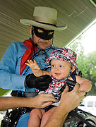 "Photo by Phil Grout..""Hey, Dad.  Who is this masked man, anyway?""  Nine-month-old .Macyn Vanderwoort of Reisterstown seems to be having a ball while.""The Lone Ranger"" and Dad wrestle to get this little doggie up.in the saddle.  ""The Lone Ranger"" visited the American Legion Post 200 in Hampstead to celebrate the American flag and commemorate the.66th anniversary of D-Day."
