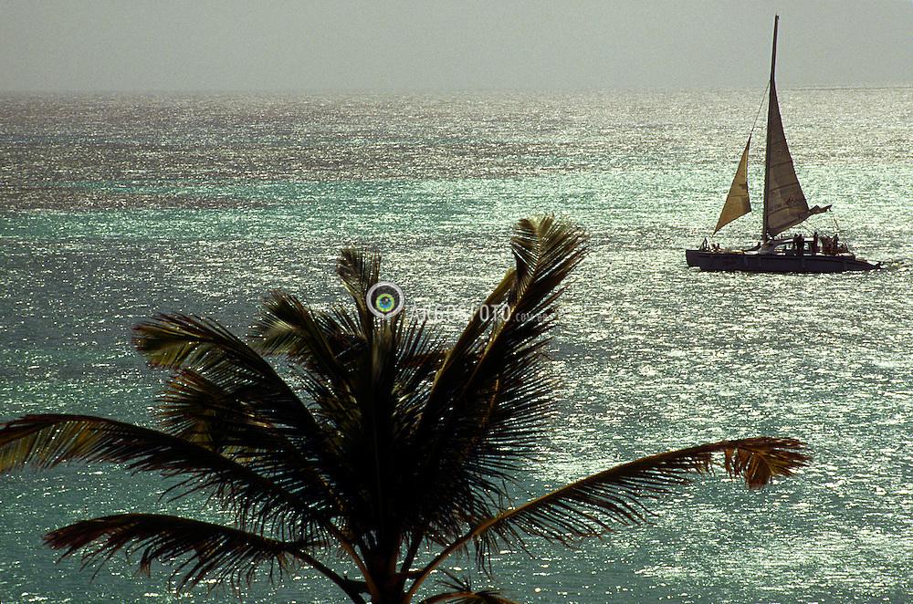 Oranjestad, Aruba. 05/1997.Barco a vela em Palm Beach, praia na capital de Aruba. Aruba e um territorio autonomo neerlandes das Caraibas, ao largo da costa da Venezuela. Alem da Venezuela, o seu vizinho mais proximo e outro territorio neerlandes: as Antilhas Holandesas. Capital: Oranjestad./ Aruba is a 32 km long island of the Lesser Antilles in the Caribbean Sea, 27 km north of the Paraguana Peninsula, Falcon State, Venezuela, and it forms a part of the Kingdom of the Netherlands. Unlike much of the Caribbean region, it has a dry climate and an arid, cactus-strewn landscape. This climate has helped tourism as visitors to the island can reliably expect warm, sunny weather..Foto Marcos Issa/Argosfoto