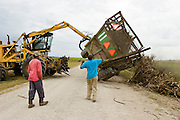 14 NOVEMBER 2005 - FRANKLIN, LA:  Workers on Jesse Breaux' sugar cane farm, right an overturned cane wagon during the 2005 sugar cane harvest. Louisiana is one of the leading sugar cane producing states in the US and the economy in southern Louisiana, especially St. Mary and Iberia Parishes, is built around the cultivation of sugar. Statewide, more than 460,000 acres of land is cultivated with sugar cane and more than 27,000 people work in the sugar industry in Louisiana. Sugar growers in the area are concerned that trade officials will eliminate sugar price supports during upcoming trade talks for the proposed Free Trade Area of the Americas (FTAA). They say elimination of price supports will devastate sugar growers in the US and the local economies of sugar growing areas. They also say it will ultimately lead to higher sugar prices for US consumers. PHOTO BY JACK KURTZ