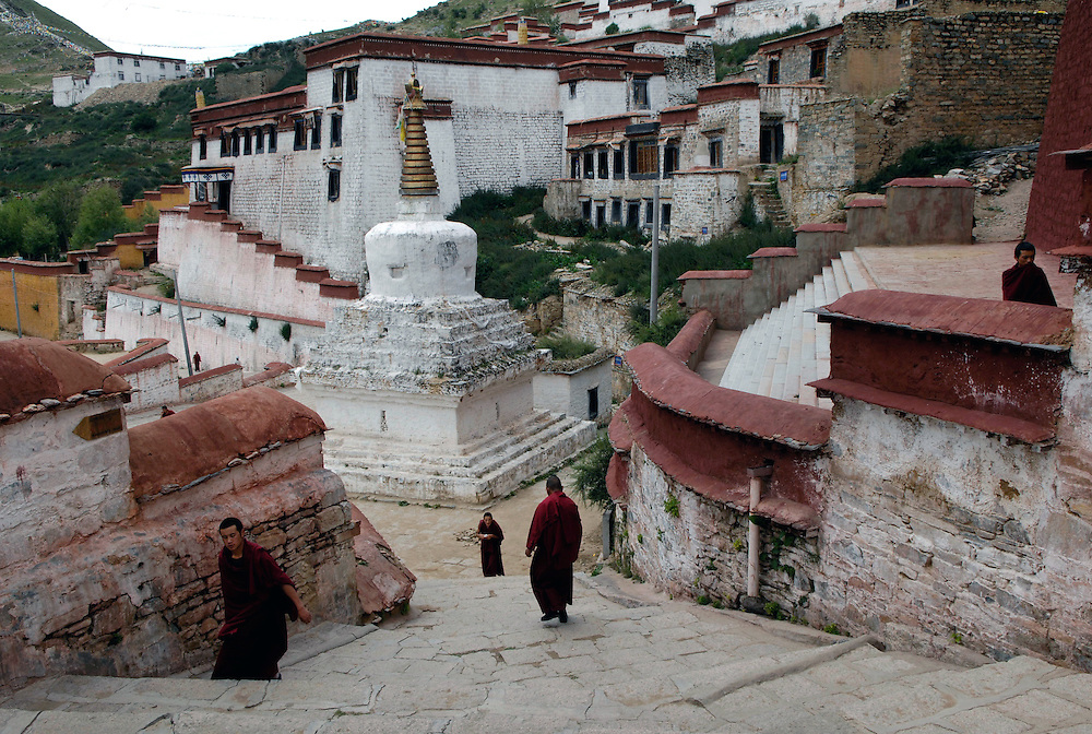 Robed monks pass through the myriad alleyways connecting the prayer halls and quarters at Ganden Monastery, one of the most important of the Gelukpa Sect (Yellow Hat). The monastery is surrounded by a kora, or holy circuit which attracts pilgrims.