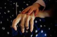 2002, Minneapolis, Minnesota, USA --- Manui Franken puts her hand on the hand of Phoebe Franken, her grandmother. -© Owen Franken