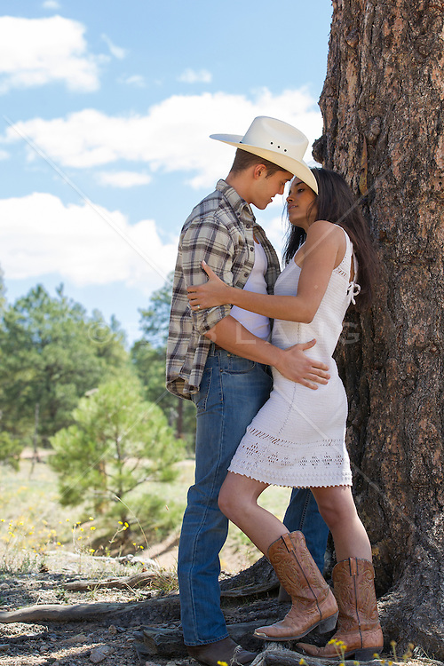cowboy and a girl about to kiss outdoors