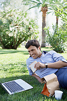Businessman using laptop while eating sandwich in park