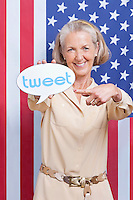 Portrait of senior woman with tweet bubble against American flag