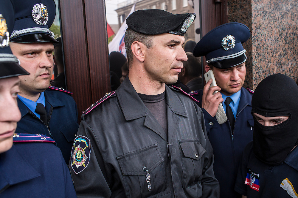 Police stand in front of the doors after pro-Russian activists took over a local police station on Thursday, May 1, 2014 in Donetsk, Ukraine.