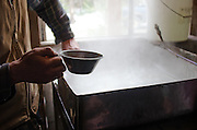 Organic farmer skimming impurities out of boiling maple sap by hand during the process of making maple syrup.