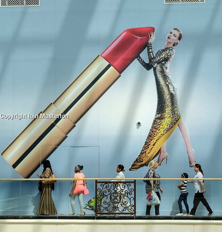 Shoppers walking beneath billboard in Mall of the Emirates shopping centre in Dubai United Arab emirates