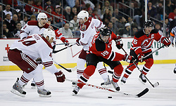 Mar 12, 2009; Newark, NJ, USA; New Jersey Devils center Travis Zajac (19) skates with the puck by Phoenix Coyotes defenseman Kurt Sauer (44) during the second period at the Prudential Center.