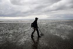 A man uses a metal detector on Barry Island beach, Wales.