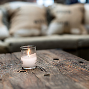 A small votive candle ssits on a rustic wooden table in a restaurant bar in front of a sofa.