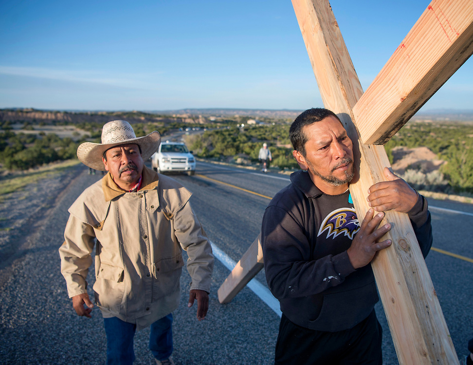 em041417a/a/Jaime Gonzales, left, and Jorge Martinez, from Santa Fe, carry a cross along Highway 503 on their way to the Santuario de Chimayo, Friday April 14, 2017. With beautiful weather, thousands of people were making the Good Friday pilgrimage to the Northern New Mexico church.  (Eddie Moore/Albuquerque Journal