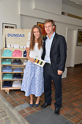 EVEIE LONGDON and MAX SANGSTER at the launch of Dundas London held at Fiskins Classic Car Showroom, 14 Queens Gate Place Mews, London on 25th June 2014.