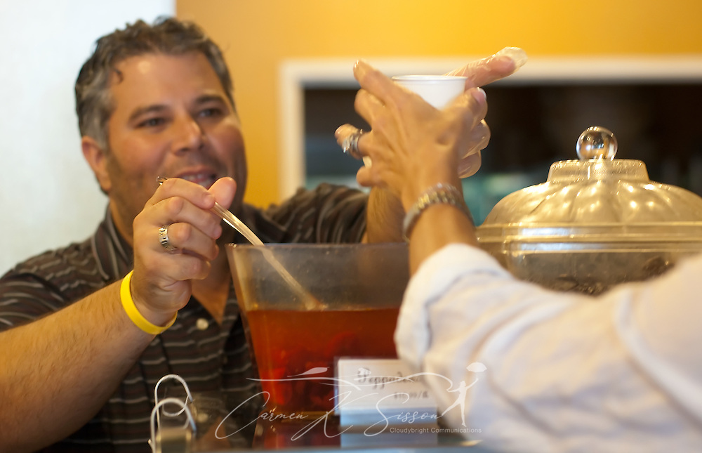 Shopkeeper Stephen Bordelon ladles gourmet olives for a customer May 8, 2011 at Epicure in Ocean Springs. The store carries more than 80 varieties of European cheese, along with other gift items. (Photo by Carmen K. Sisson/Cloudybright)