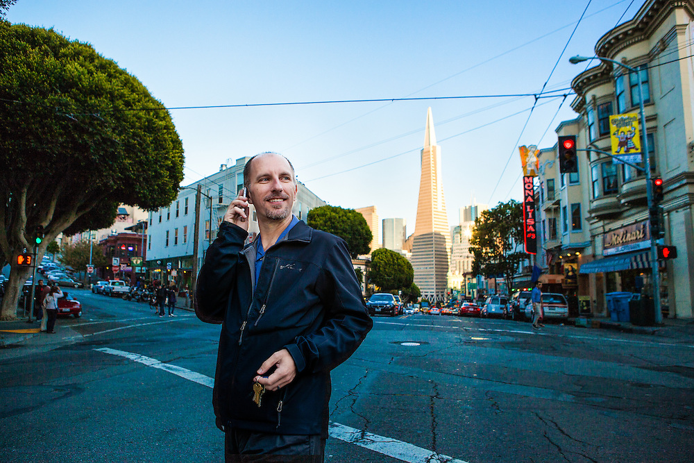 Lifestyle & Editorial Photography for CARMAnation.com. Man crossing the street in North Beach, talking on his phone with Trans America Building in the background. Active urban scene.