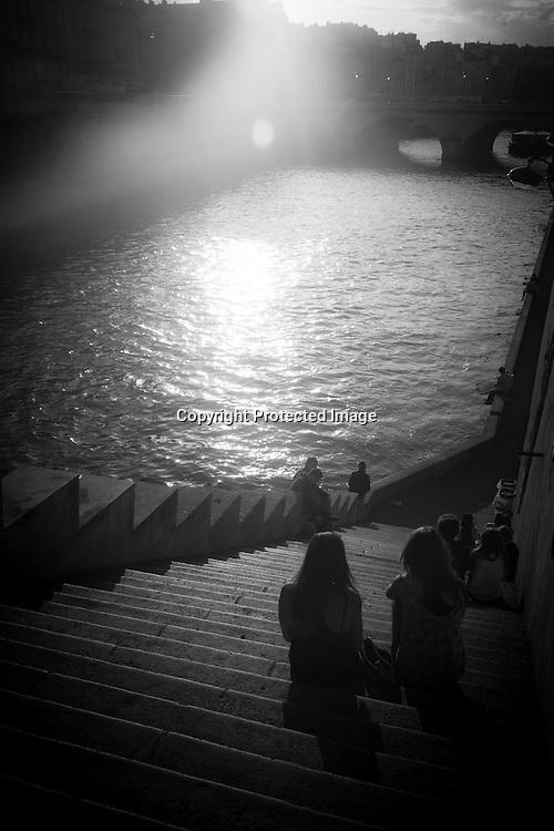 France. Paris. 4th district. people enjoying sunset on the quay notre dame, by the seine river / les gens se pressent sur le quai notre dame pour profiter du soleil. paris  at sunset