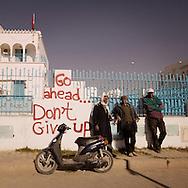 "TUNISIA, SIDI BOUZID : Men stand next to a graffiti reading ""Go ahead...don't give up"" in Sidi Bouzid. Copyright Christian Minelli."