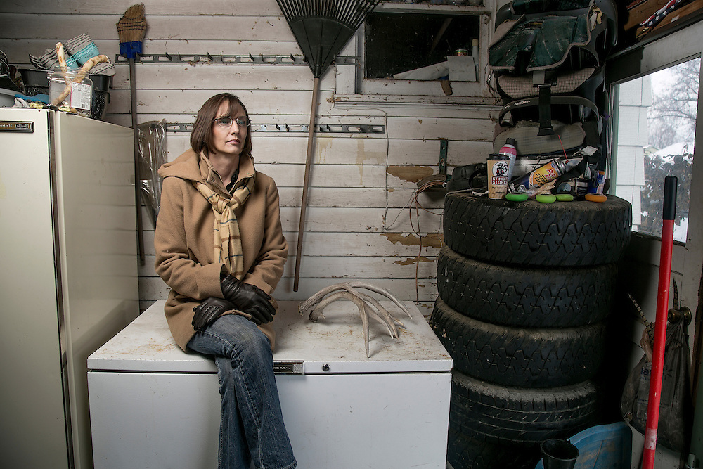 """NAMPA, IDAHO - JANUARY 19 : Chelle Gluch sits on a freezer in her garage where she keeps deer meat that helps reduce her family's food budget expenditures for the year in Nampa, Idaho on January 19, 2017.  Chelle supplements her food income by hunting, fishing, foraging for mushrooms and caring for a brood of chickens. Chelle runs a home day care business and was an Idaho District 12 Senate candidate in 2016. Chelle doesn't have health insurance and is one of over 78,000 Idahoans who fall in the Medicaid gap. """"I am sick and tired of poor people being marginalized. I average $1.50 per hour per kid in my daycare. I work 14-16 hours a day. Health care is a basic human right.  I have had my house egged, my car vandalized and been called a """"welfare rat"""" by people who oppose my support for Obamacare. (Poor people) are worthy of a little bit of assistance."""" Gluch said about Obamacare and the Republican attempt to replace the program. (Photo by Kyle Green for The Washington Post)"""