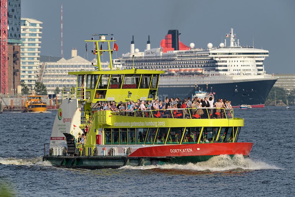 Die Queen Mary II legt vom Terminal Hafencity neben dem Unilever-Gebäude, dem Marco-Polo-Turm und der immer noch im Bau befindlichen Elbphilharmonie ab.  Im Vordergrund kreuzt eine mit Touristen vollbesetzte Hafenfähre.